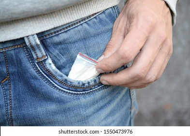 Male hand retrieving drug packet our of blue jean pocket with copy space on abandoned building background