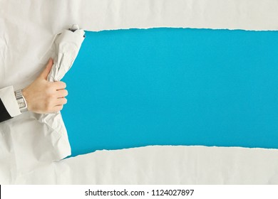 male hand ripping a paper sheet revealing a blank blue surface