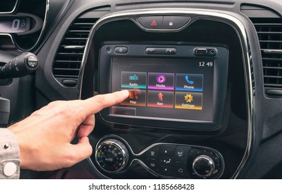 Male hand selects a map on a multimedia system in the car