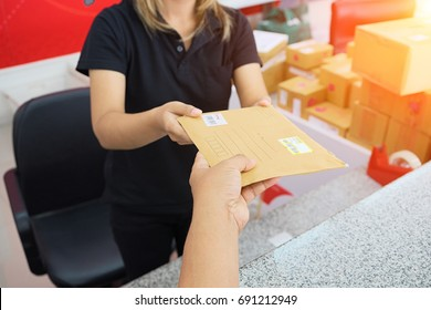 male hand send mail envelope to the female of post office before sending .