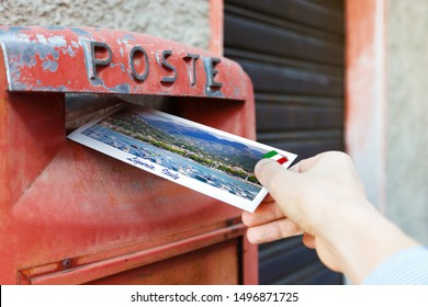 Male hand sends a postcard to a red mailbox in Liguria region, Italy. The postcard shows a Liguria coast, Sestri Levante city