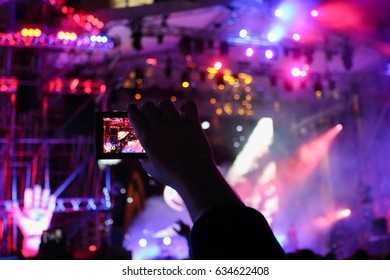 Male hand shoots video by phone during concert with laser show at night