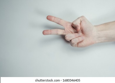 Male hand show two fingers up isolated on a white background. Symbols of the finger of the world are the forces of struggle, the symbol of victory, the letter V in sign language or number two or two.