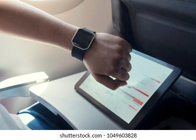 Male hand with smart watch on wrist. Planning agenda and schedule using calendar event planner. Calender planner of travel on airplane.