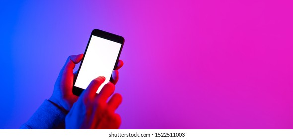 Male hand with smartphone. Blank white screen. Mock-up. Red and blue neon light.