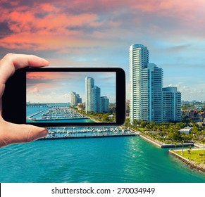 Male hand with smartphone taking a picture of Miami from cruise ship. Tourism concept.