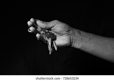 A male hand with some keys black and white