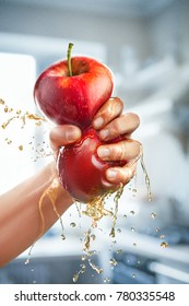A male hand squeezes fresh juice. Pure apple juice pouring out from fruit into glass
