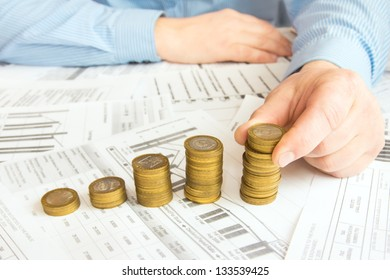 Male hand stacking  gold coins into increasing columns over different paper documents background. Earnings or saving graph (diagram).