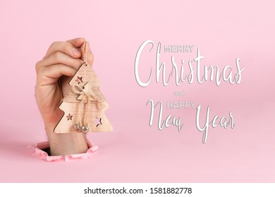 A male hand sticks out of hole in paper, holds a Christmas tree ornament. Christmas concept symbol, commercial bucket print, copy space.