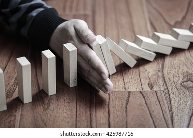 A male hand stopping the domino effect. Risk control and Solution concept.