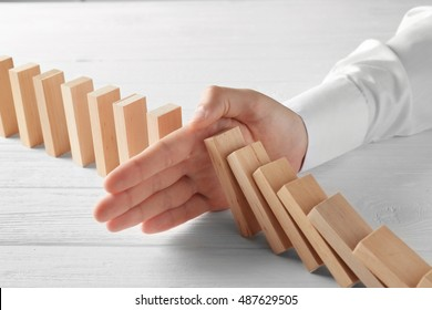 Male hand stopping domino effect on wooden table