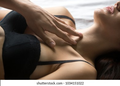 Male hand stroking female chest, passionate lover caressing arousing beautiful woman lying on bed in black bra lingerie, man enjoying foreplay with sexy lady, sensual stimulation concept, close up