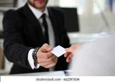 Male hand in suit give blank calling card to female visitor closeup. White collar partners company name exchange, executive or ceo introducing at conference, product consultant, sale clerk concept