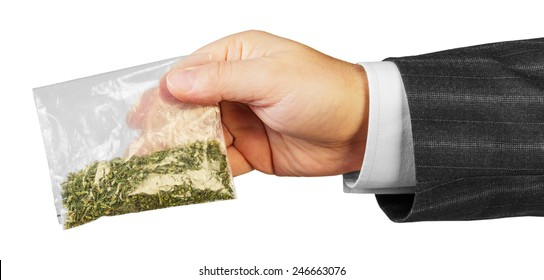 Male hand in suit with package of drugs isolated on white background