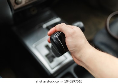 Male hand switches automatic transmission closeup. Close up view of gear lever manual transmission car interior parts.
