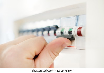 Male hand switching off fuse board.