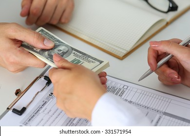 Male hand taking or giving bunch of hundred dollars bank notes to woman closeup. Female hand accepting cash payment from man. IRS, bribe and bribery, collusion, crime, revenue report concept