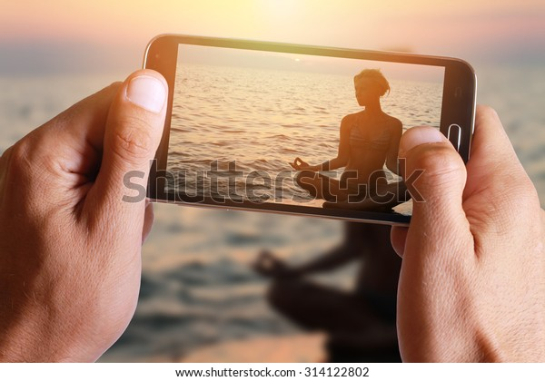 Male hand taking photo of Yoga woman meditating in lotus pose on the beach during sunset with cell, mobile phone.