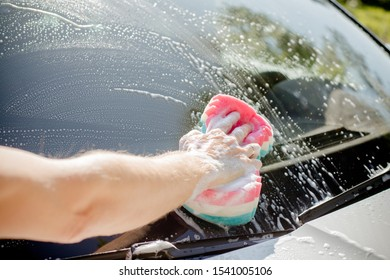 Male hand with tool for washing windows, car wash.man washing a soapy blue car with colorful sponge.Man washing car with a sponge and foam in the house yard.Manual auto wash shop service