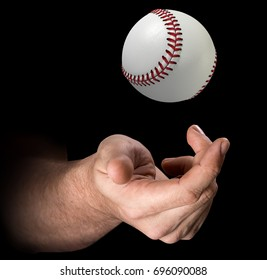 A male hand tossing a baseball up in the air on an isolated dark background - 3D render