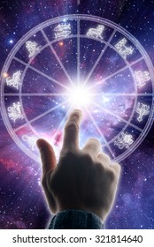 male hand touching an astrology chart - background image provided by NASA