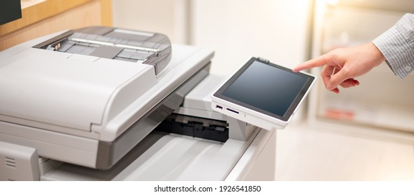 Male hand touching button on control panel of photocopier copying and printing report paperwork in office. Electronic equipment and supply for business organization.