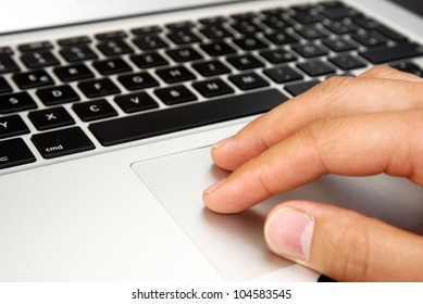 male hand with touchpad on silver laptop with black keys