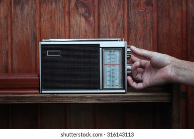 Male hand tuning the old receiver with analogue scale, listening news or music, next to wooden wall
