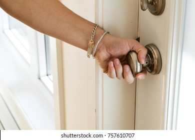 Male hand turning brass doorknob. Opening the front door of the house.