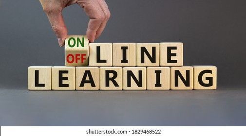 Male hand turns the cube and changes the expression 'offline learning' to 'online learning'. Beautiful grey background. Business and education concept. Copy space.