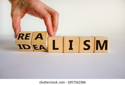Male hand turns cubes and changes the expression 'idealism' to 'realism' or vice versa. Beautiful white background. Business concept. Copy space.