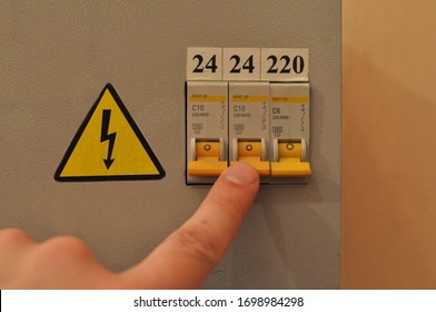 The male hand turns off the toggle switch of the residual current device.