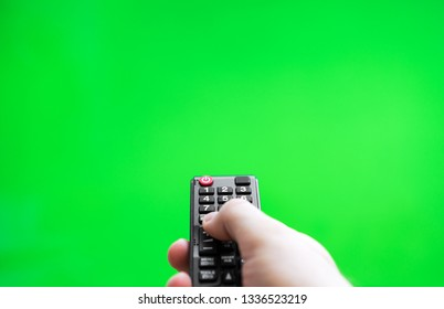 Male hand with TV remote control over green screen. Place for your advertisement.