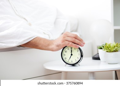 Male hand under blanket reaching out for alarm clock, shallow depth of field focus on foreground
