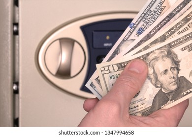 Male hand with US dollars on the background of the safe with the door open. Storage of banknotes in a box with a code number. The concept of saving money, service in a hotel or bank.