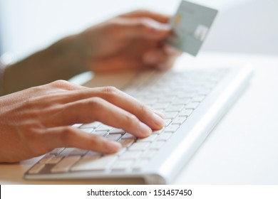 Male hand using computer keyboard and holding credit card for online payment
