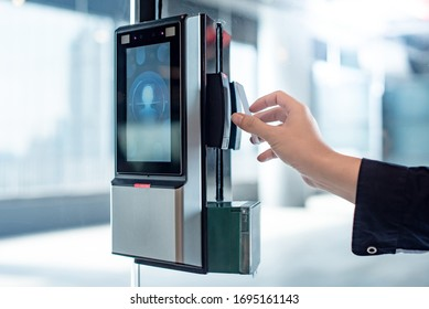 Male hand using key card to open smart door lock for security system on glass door in office building. Biometric authentication device for privacy and safety.