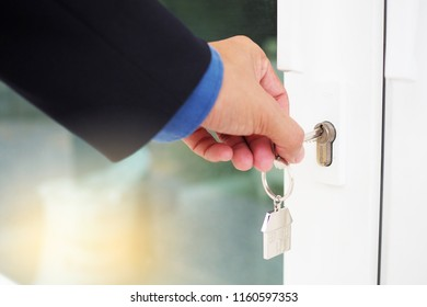 The male hand is using the key to open his own house. New home, home and homeownership concept