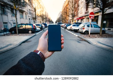 Male hand using smart phone on the street. Concept of technology and social network. Business man with watches, coat and take a photo.