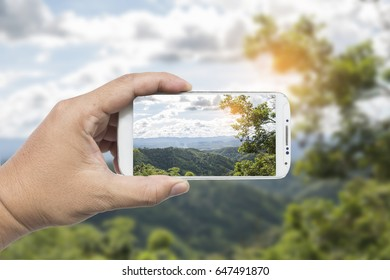 Male hand using smart phone with take photo at beautiful mountain in Thailand