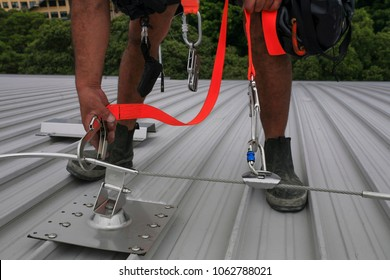 Male hand using transfer, clipping stainless industrial locking hook into the fall arrest roof anchor point systems, while tail is connected into his body personal safety harness in Sydney, Australia