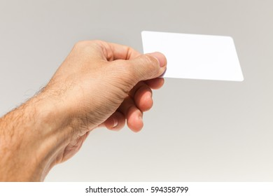 Male hand with white empty card over gray wall background, closeup photo with selective focus