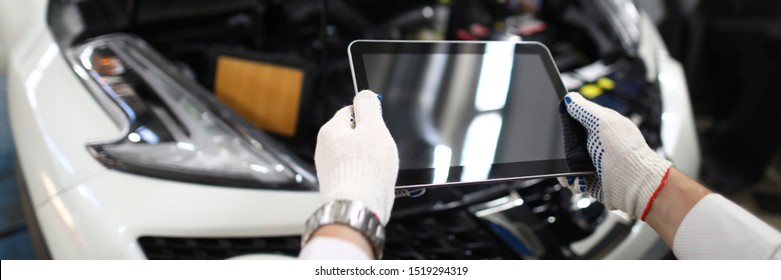 Male hand in white protective gloves hold digital lablet in hand against car service station background. Engineer support system information diagnostic. Automotive station check concept