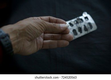 A male hand with a withe medicine tablet