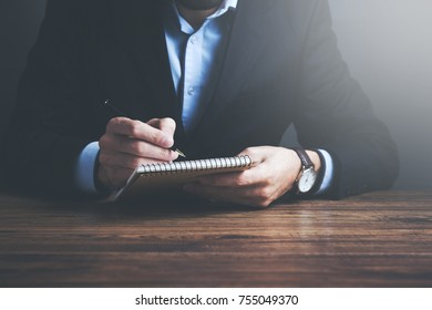 male hand is writing in  notepad on a wooden table