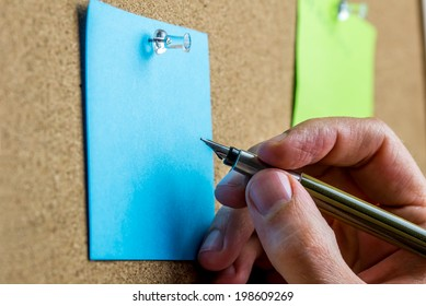 Male hand writing on blank sheet of blue paper with copyspace pinned up on a cork bulletin board.