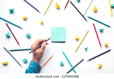 Male hand writing on notepaper with colorful pencil on white background.Business creativity and education ideas concepts