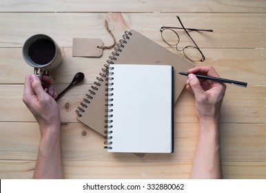 Male hand writing on opened notebook with a cup of coffee on wooden table. Top view. Writing concept