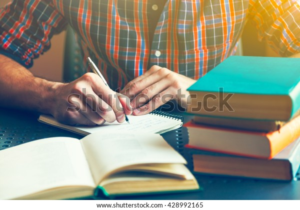 male hand writing with pen near books